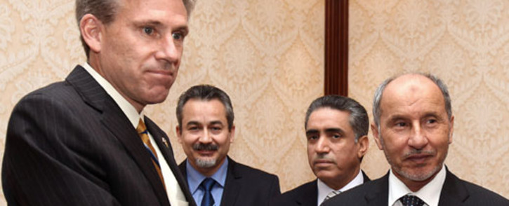 The late US ambassador to Libya, J. Christopher Stevens shaking hands with Libyan National Transitional Council (NTC) chairman Mustafa Abdel Jalil. Picture: AFP.