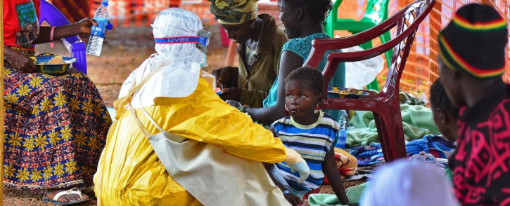 An MSF medical worker feeds an Ebola child victim at an MSF facility in Kailahun, Sierra Leone on 15 August, 2014. Picture: AFP.