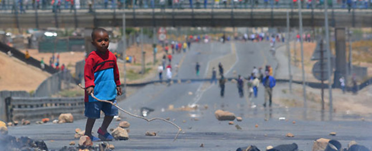 A small boy walks among the rubble strewn across the N1 highway at De Doorns on 9 January 2013. Picture: Aletta Gardner/EWN