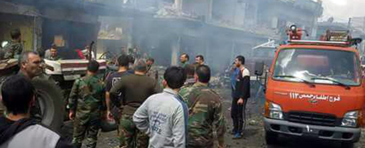 A handout image released by the official Syrian Arab News Agency on 5 May, 2016 shows Syrian security members gather at the site of a bomb attack in Mukharram al-Fawqani in Homs province. Picture: AFP.