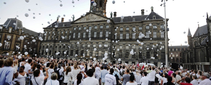FILE: People release white balloons in the air during a silent march in memory of the victims of the downed Malaysia Airlines flight MH17, on 23 July 2014. Picture: AFP.