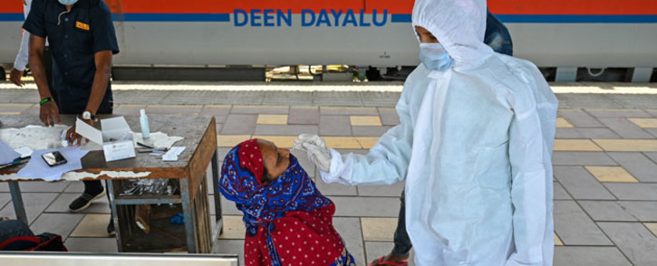 A health worker takes a nasal swab sample of a passenger for the COVID-19 coronavirus test after arriving at a railway platform on a long-distance train, in Mumbai on 14 April 2021. Picture: Punit Paranjpe/AFP