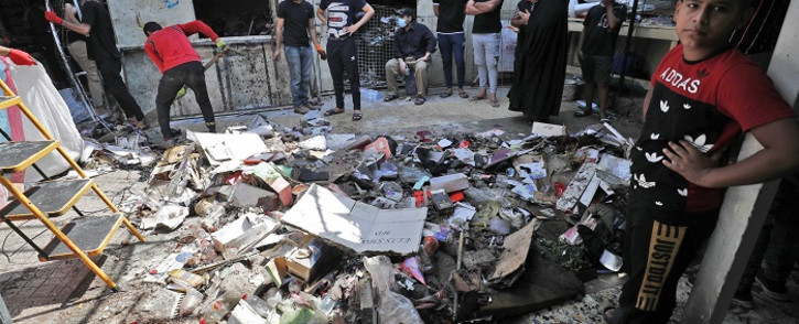 Iraqis inspect the site of the explosion a day earlier in a popular market in the Shiite-majority Sadr City neighbourhood, east of the capital Baghdad on July 20, 2021. Iraq was in mourning for at least 36 people killed when a bomb ripped through a crowded Baghdad market in what the Islamic State group's jihadists claimed as a suicide attack. Picture: Ahmad Al-Rubaye / AFP