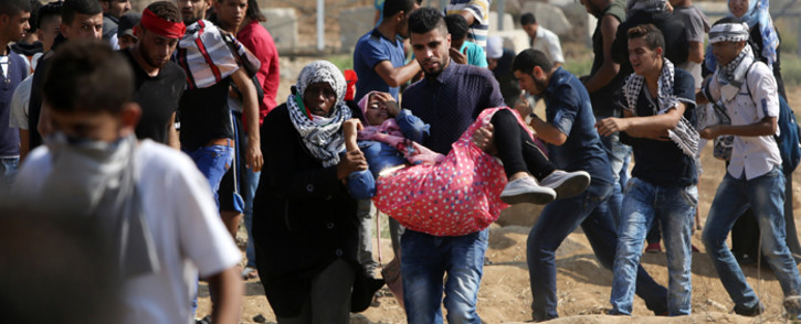 A Palestinian protester is evacuated by comrades after being injured by a tear gas canister during clashes with Israeli security forces near the Nahal Oz border crossing with Israel, east of Gaza City on 10 October, 2015. Picture: AFP.
