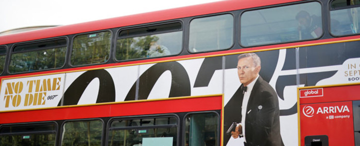 A London red bus goes past a street with a poster of the latest James Bond film 'No Time To Die' in London on 4 October 2021. Picture: Tolga Akmen/AFP
