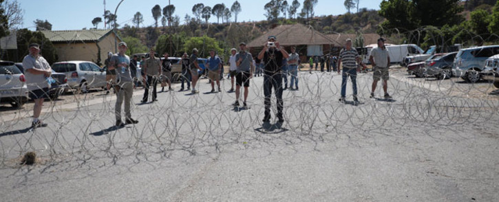 Farmers protest behind a police barrier of razorwire during the court appearance of two suspects accused of murdering farm manager Brendin Horner in Senekal in the Free State on 16 October 2020. Picture: Abigail Javier/EWN