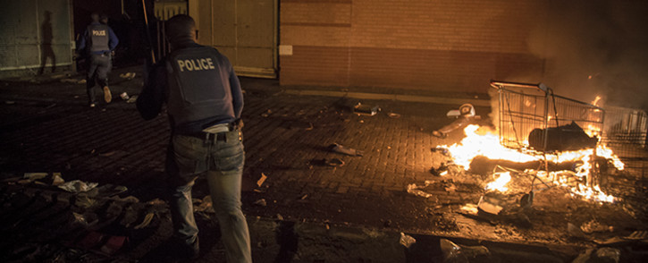 Looters attempt to distract police by lighting fires but police disperse them from the Mabopane Central City Mall. Picture: Thomas Holder/EWN.