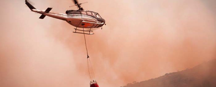 A helicopter carrying hundreds of litres of water fights a massive blaze in Glencairn, Cape Town. Picture:DreamImages/EWN.