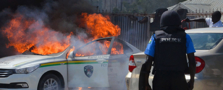 A Nigerian police officers watches a police vehicle as it goes up in flames following clashes with supporters of Islamic Movement of Nigeria (IMN) protesting against the imprisonment of their leader Ibrahim Zakzaky, in Abuja, on 30 October 2018. Piture: AFP.