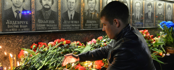 A man lights a candle amid flowers in front of the monument to Chernobyl victims in Slavutich, some 50 km from the accident site, and where many of the power stations personnel used to live, during a memorial ceremony early on 26 April, 2016. Picture: AFP.