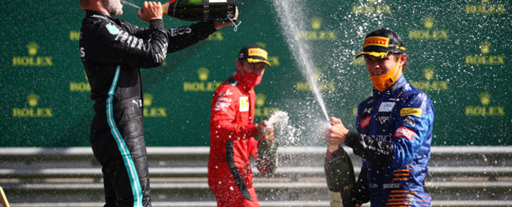 (L-R) Mercedes' Finnish driver Valtteri Bottas, Ferrari's Monegasque driver Charles Leclerc and McLaren's British driver Lando Norris celebrate with champagne on the podium after the Austrian Formula One Grand Prix race on 5 July 2020 in Spielberg, Austria. Picture: AFP