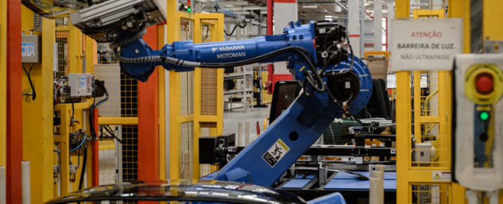 A robot arm carries a glass part in the assembly line of a factory. Picture: AFP