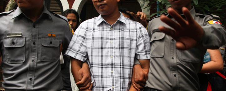 Detained Myanmar journalist Wa Lone, 32, is seen handcuffed and escorted by police while leaving Yangon courthouse after the first day of trial on 16 July 2018. Picture: AFP