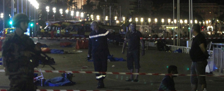 Soldiers, police officers and firefighters walk near dead bodies covered with a blue sheets on the Promenade des Anglais seafront in the French Riviera town of Nice on 15 July, 2016. Picture: AFP.