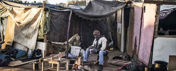 FILE: Lucky, 55, brews some tea to warm up in the bitter cold in Wilgespruit, Johannesburg, on 28 May 2020. Picture: AFP