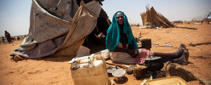 A handout picture released by the United Nations-African Union Mission in Darfur (UNAMID) on 28 May 2014 shows Aisha Abdala, a displaced woman from Katila, South Darfur, cooking next to her shelter at the al-Sereif camp for Internally Displaced Persons (IDP) in Nyala, South Darfur. Picture: AFP.