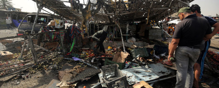 FILE: Iraqis check the damage after a suicide bomber detonated an explosives-rigged vehicle in northern Baghdad's Sadr City on 17 May 2016 security and medical officials said. Picture: AFP/Ahmad al-Rubaye