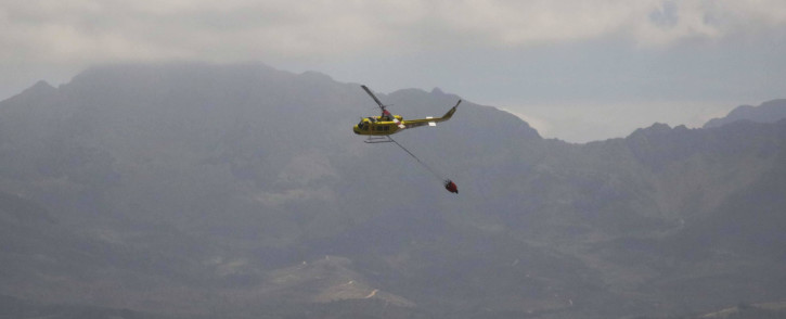 FILE: A helicopter water bombs a wildfire. Picture: EWN
