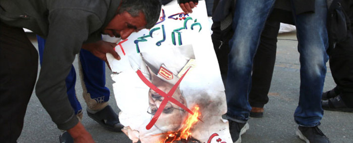 Libyans burn a picture of strongman Khalifa Haftar during a rally in support of the UN-recognised Tripoli-based government, in the capital Tripoli on 3 January 2020. Picture: AFP