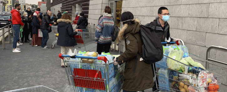 People using protective masks leave a supermarket with trolleys full of shopping in Milan on 8 March 2020 as Italy quarantines more than 10 million people around the financial capital Milan and the tourist mecca Venice for nearly a month to halt the spread of the novel coronavirus, COVID-19. Picture: AFP