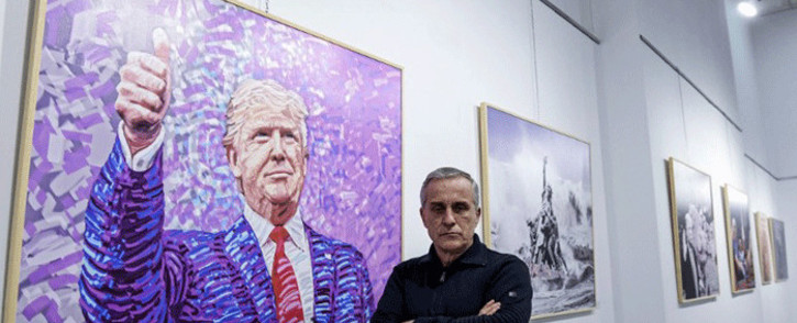 "Albanian artist Avni Delvina poses for a photo in front of his paintings during the exhibition 'The Donald' in Tirana on February 21, 2019. Donald Trump as Rambo or as Jesus crucified: a painter dedicated fifty paintings to the American president, his ""idol"", which are on display in the Albanian capital. Picture: AFP."