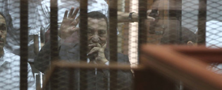Egypts deposed president Hosni Mubarak waves from behind the accused cage during his trial on 21 May, 2014 in Cairo. An Egyptian court sentenced Mubarak to three years in prison on corruption charges, in one of two trials after the 2011 uprising that ended his rule. Picture: AFP.