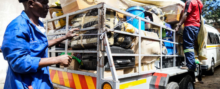 Transporters from South Africa on 19 February 2019 unload a trailer loaded with goods for delivery in Bulawayo and surrounding townships. Items are loaded in Johannesburg onto trailers attached to minibuses which make the 550 kilometres journey north to the border of Zimbabwe, where the economic situation has dramatically deteriorated, pushing inflation above 50%, and shortages of household essentials have become widespread. Picture: AFP