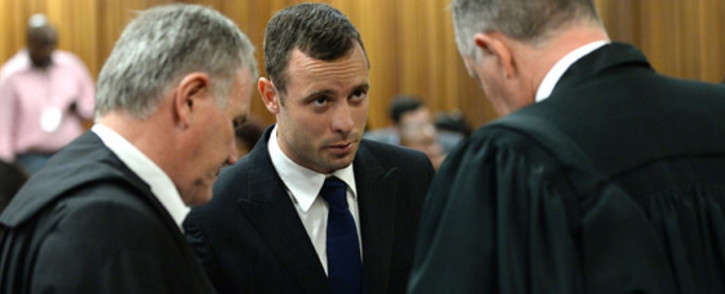 FILE: Oscar Pistorius in conversation with his legal team Barry Roux (left) and Kenny Oldwage (right) on the second day of his murder trial in the North Gauteng High Court in Pretoria on 4 March 2014. Picture: Pool.