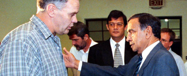 FILE: Former Transport Minister Dullah Omar (R) makes a concilliatory gesture to convicted killer and former apartheid assassin Ferdi Barnard (left) during a break at a hearing of the Truth and Reconciliation Commission (TRC) in Cape Town 02 October 2000. Ferdi Barnard applied for amnesty for the attempted murder of Omar. Picture: AFP