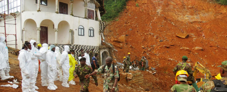 Search and rescue team members and soldiers operate near a mudslide site and damaged building near Freetown, Sierra Leone on August 15, 2017. Picture: AFP