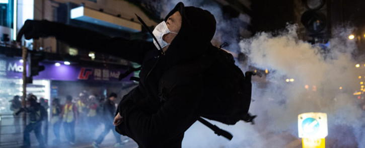 A protester reacts after police fire tear gas to disperse bystanders in a protest in Jordan district in Hong Kong, on early 25 December 2019. Picture: AFP
