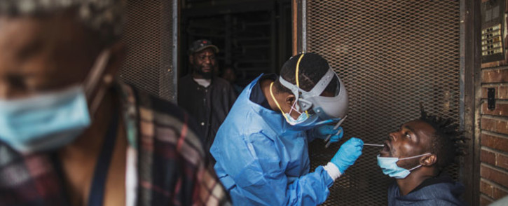 FILE: A Gauteng Health Department official collects samples from a man during a door-to-door COVID-19 coronavirus testing drive in Yeoville, Johannesburg, on 3 April 2020. Picture: AFP