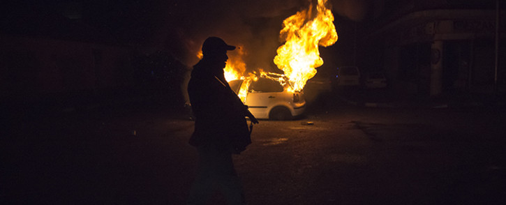 A police officer passes by a burning car in Jeppestown during xenophobic violence on 16 April 2015. Picture: Thomas Holder/EWN.