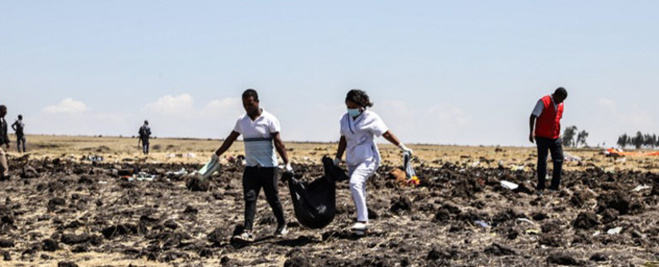 FILE: Rescue team members carry bodies in bags at the crash site of an Ethiopian Airlines Boeing 737 MAX. Picture: AFP
