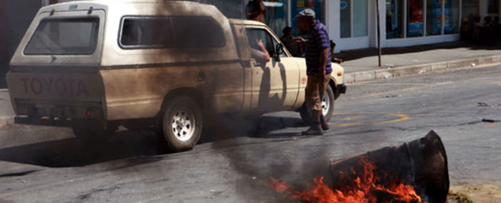 A protester confronts a farmer in a bakkie while others (unseen) block the main road in Swellendam with burning obstacles on Thursday, 15 November 2012 during widespread unrest among farm workers that started in De Doorns in the Western Cape and since spread to other towns in the area. Picture:Nardus Engelbrecht/SAPA.