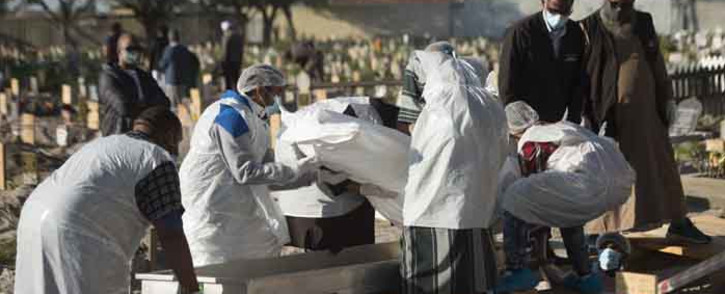 FILE: Members of a family dressed in personal protective equipment put the body of a man who died of COVID-19 into a grave during a Muslim burial at the Klip Road Cemetery in Grassy Park, Cape Town, on 9 June 2020. Picture: AFP.