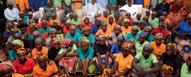 A handout picture released by the PGDBA&HND Mass Communication/Sunday Aghaeze shows Nigeria's President Muhammadu Buhari (C) sitting among the 82 rescued Chibok girls during a reception ceremony at the Presidential Villa in Abuja, on 7 May 2017. Picture: AFP