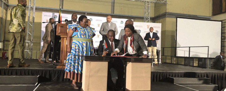 President Cyril Ramaphosa, surrounded by government officials and union representatives, signs the National Minimum Wage Bill into law. Picture: @SAgovnews/Twitter.