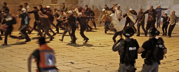 Palestinian protesters rush away amid clashes with Israeli security forces at the al-Aqsa mosque compound in Jerusalem, on 7 May 2021. Picture: Ahmad GHARABLI/AFP