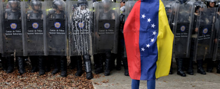 FILE: A Venezuelan student stands in front of riot police during a protest against the government of President Nicolas Maduro, in Caracas on 12 March 2014. Picture: AFP.