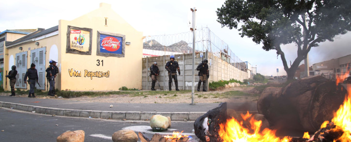 FILE: Police positioned on a corner watch amid protests in Hangberg. Picture: EWN.