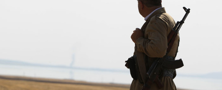 FILE: A Kurdish peshmerga fighter looks at smoke rising in the horizon following US airstrikes targeting Islamic State (IS) militants at Mosul Dam on 18 August 2014. Picture: AFP