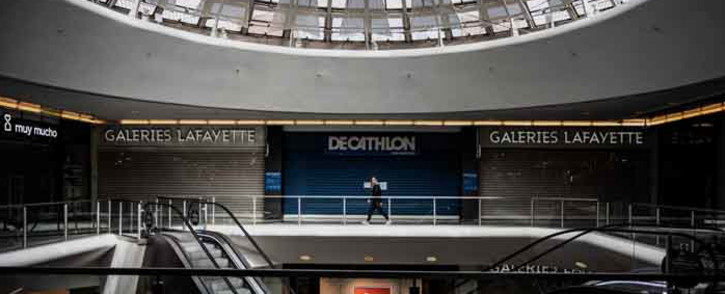 FILE: A person walks in the empty Lyon Part Dieu mall in Lyon on 17 March 2020, as a strict lockdown comes into effect in France to stop the spreading of COVID-19, caused by the novel coronavirus. A strict lockdown requiring most people in France to remain at home came into effect at midday on 17 March 2020, prohibiting all but essential outings in a bid to curb the coronavirus spread. Picture: AFP.