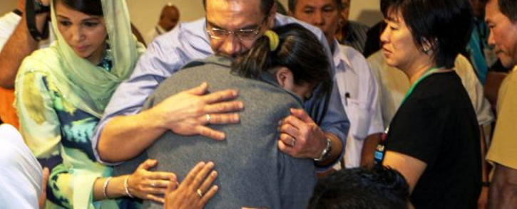 Malaysia's Minister of Defence and Acting Transport Minister Hishammuddin Hussein (C) hugs a relative of the missing Malaysia Airlines flight MH370 during his visit at a hotel in Putrajaya on March 29, 2014. Picture: AFP.