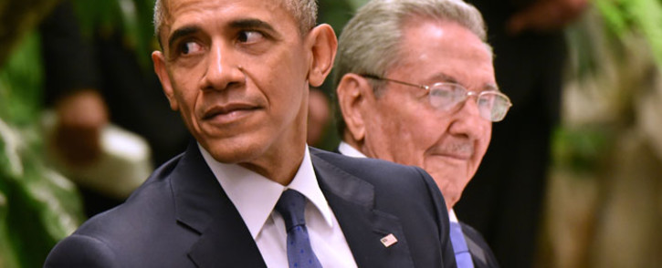 FILE: Sitting next to Cuban President Raul Castro (R), US President Barack Obama (L) gestures during the state dinner at the Revolution Palace in Havana on 21 March 2016. Picture: AFP/Adalberto Roque.