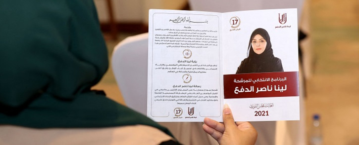 A woman holds a leaflet for the candidate for Qatar's Shura council elections in the 17th constituency, Leena Nasser al-Dafa, during a campaign event in Doha, on September 26, 2021, ahead of Qatar's inaugural legislative polls. Picture: AFP