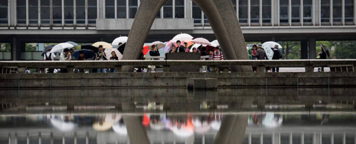 Visitors stand in front of the Hiroshima Peace Memorial park cenotaph in Naka Ward, Hiroshima Prefecture on 25 May, 2016. Picture: AFP.