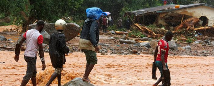 Residents walk through floodwaters past a damaged building in an area of Freetown on 14 August 2017 after landslides struck the capital of the west African state of Sierra Leone. Picture: AFP