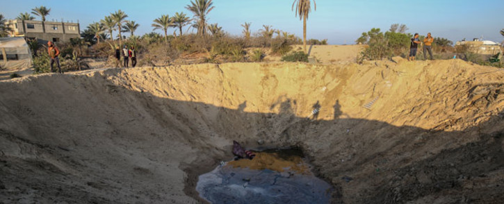 FILE: Palestinian men walk around a crater caused by an Israeli airstrike launched in response to rocket fire, in Khan Yunis in the southern Gaza Strip on 2 November 2019. Picture: AFP