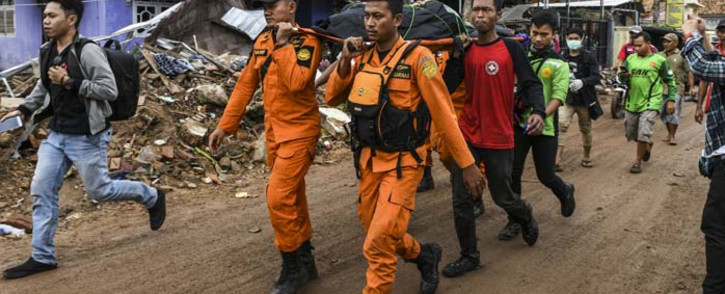 "Members of an Indonesian search and rescue team carry the body of a victim, retrieved from a collapsed home, in a body bag in Rajabasa in Lampung province on 25 December 2018, three days after a tsunami - caused by activity at a volcano known as the ""child"" of Krakatoa - hit the west coast of Indonesia's Java island. Picture: AFP"